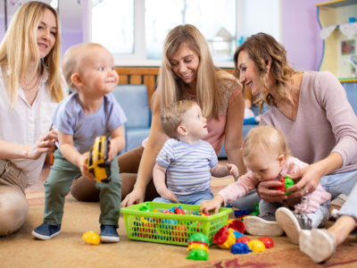 babies playing toys with young ladies